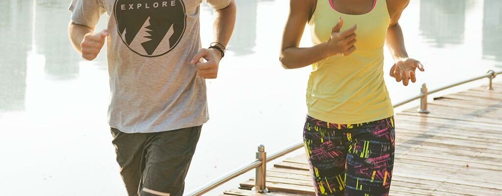Couple running together on a boardwalk